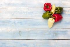 在一个蓝色木板的五颜六色的胡椒 库存照片