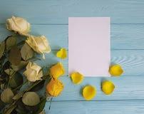 在一个蓝色木背景地方的白色和黄色玫瑰秀丽文本空白白色卡片的 库存照片