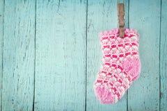 在一个蓝色木背景的桃红色婴孩袜子 库存图片