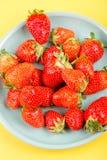 在一个蓝色杯子的新鲜的草莓在黄色背景 库存照片