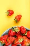 在一个蓝色杯子的新鲜的草莓在黄色背景 免版税库存图片