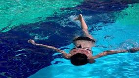 在一个蓝色水池的年轻女人游泳 影视素材