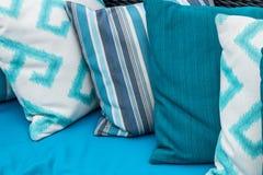 在一个蓝色沙发的五颜六色的枕头 白色,蓝色,深蓝 免版税库存照片