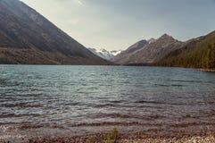 在一个蓝色湖后的一座山 库存照片
