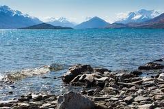 在一个蓝色湖附近的斯诺伊山 免版税库存图片