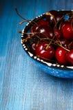 在一个蓝色碗特写镜头的樱桃在蓝色 免版税库存图片