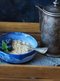 在一个蓝色碗的新鲜的燕麦粥用蓝莓和一个老咖啡罐 免版税库存照片