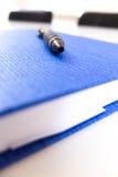 在一个蓝色笔记本的黑笔 免版税库存图片