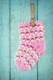 在一个蓝色背景的桃红色婴孩袜子 库存照片
