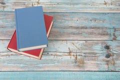 在一个蓝色脚手架木地板上的红色和蓝皮书与空间 库存图片