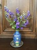 在一个蓝色花瓶的紫色响铃 免版税库存照片