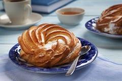 在一个蓝色茶碟的奶油色蛋糕 免版税库存照片