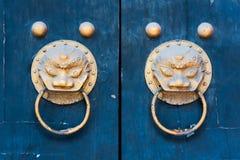 在一个蓝色裂缝的两个龙中国金黄色的通道门环 库存图片