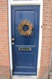 在一个蓝色门的金黄花圈 免版税库存图片