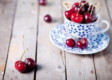 在一个蓝色陶瓷杯子的新鲜的樱桃 免版税库存照片