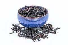 在一个蓝色陶瓷碗的中国人Oolong深红茶武夷Rou gui 免版税库存照片