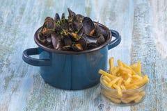 在一个蓝色陶瓷罐的淡菜在蓝色木背景 使用一个玻璃碗炸薯条 Brlgium生活方式 免版税库存照片