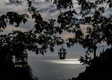 在一个藤和灯笼剪影下的日落与海 免版税库存照片