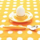 在一个蛋杯的一个煮沸的鸡蛋在黄色弄皱的被加点的布料 minim 免版税库存照片