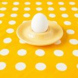 在一个蛋杯的一个鸡蛋在黄色弄皱的被加点的布料 库存照片