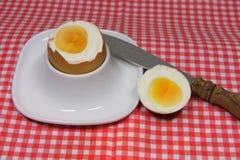 在一个蛋杯的金黄鸡蛋在红色仿造了与匙子的餐巾 免版税库存照片