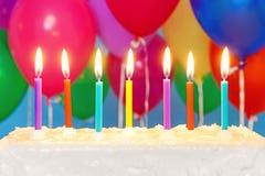 在一个蛋糕的蜡烛与气球在背景中 库存图片
