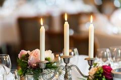 在一个蜡烛台的三个蜡烛在装饰的桌上 免版税库存图片