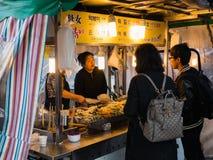 在一个街道食物摊位的人买的食物在Hongdae街道 库存图片