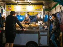 在一个街道食物摊位的人买的食物在Hongdae街道 免版税图库摄影