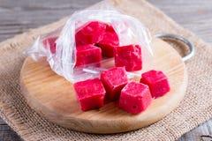 在一个袋子的冻莓果立方体在桌上的一个切板 免版税库存图片