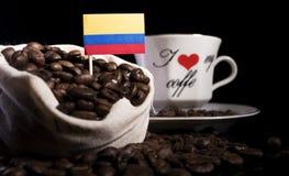 在一个袋子的哥伦比亚的旗子用在黑色隔绝的咖啡豆 免版税库存照片