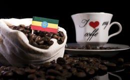 在一个袋子的埃赛俄比亚的旗子用在黑色隔绝的咖啡豆 免版税库存图片