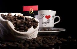 在一个袋子的安哥拉旗子用在黑色隔绝的咖啡豆 免版税库存图片