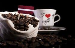 在一个袋子的拉脱维亚旗子用在黑色的咖啡豆 免版税库存图片