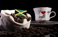 在一个袋子的牙买加旗子用在黑色的咖啡豆 免版税库存图片