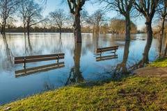 在一个被充斥的河岸的被淹没的长凳 免版税库存照片