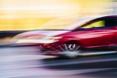 在一个被弄脏的城市场面的红色跑车 免版税库存图片