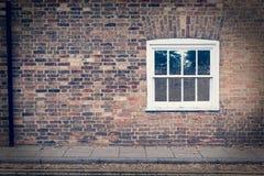 在一个被恢复的砖墙上的白色木上下开关窗 免版税库存照片