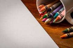 在一个被打翻的杯子的蜡笔在纸旁边 免版税库存图片