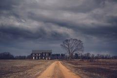 在一个被放弃的农厂房子的不祥的云彩 库存图片