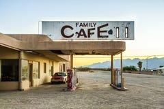在一个被放弃的加油站的被击毁的汽车在荒废村庄 免版税图库摄影