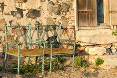 在一个被放弃的小屋之外的两把绿色椅子在堡垒 库存图片