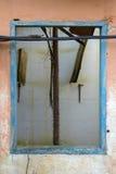 在一个被放弃的房子的橙色墙壁上的老木蓝色窗架 库存照片