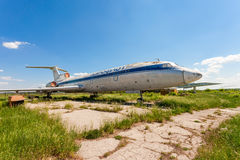 在一个被放弃的机场的老俄国航空器图-154 免版税库存图片
