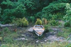 在一个被放弃的水池的老小船 库存图片