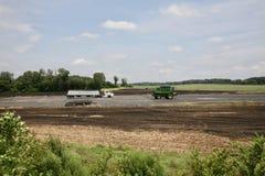 在一个被烧的庄稼领域的农场设备 免版税库存照片