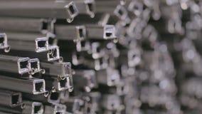 在一个被盖的仓库里描出管子,在行放置的外形管子在一个大仓库,有金属的仓库里 股票视频