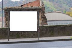 在一个被破坏的房子前面的空白的广告牌 免版税图库摄影