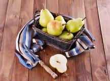 在一个被编织的篮子的有机梨在木背景 免版税库存照片