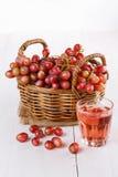 在一个被编织的篮子的红葡萄与杯汁液 免版税库存图片